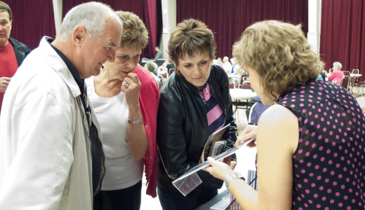Dianne showing photos to Dale's cousins in Medicine Hat at the BMF Gospel Jamboree, 2013.