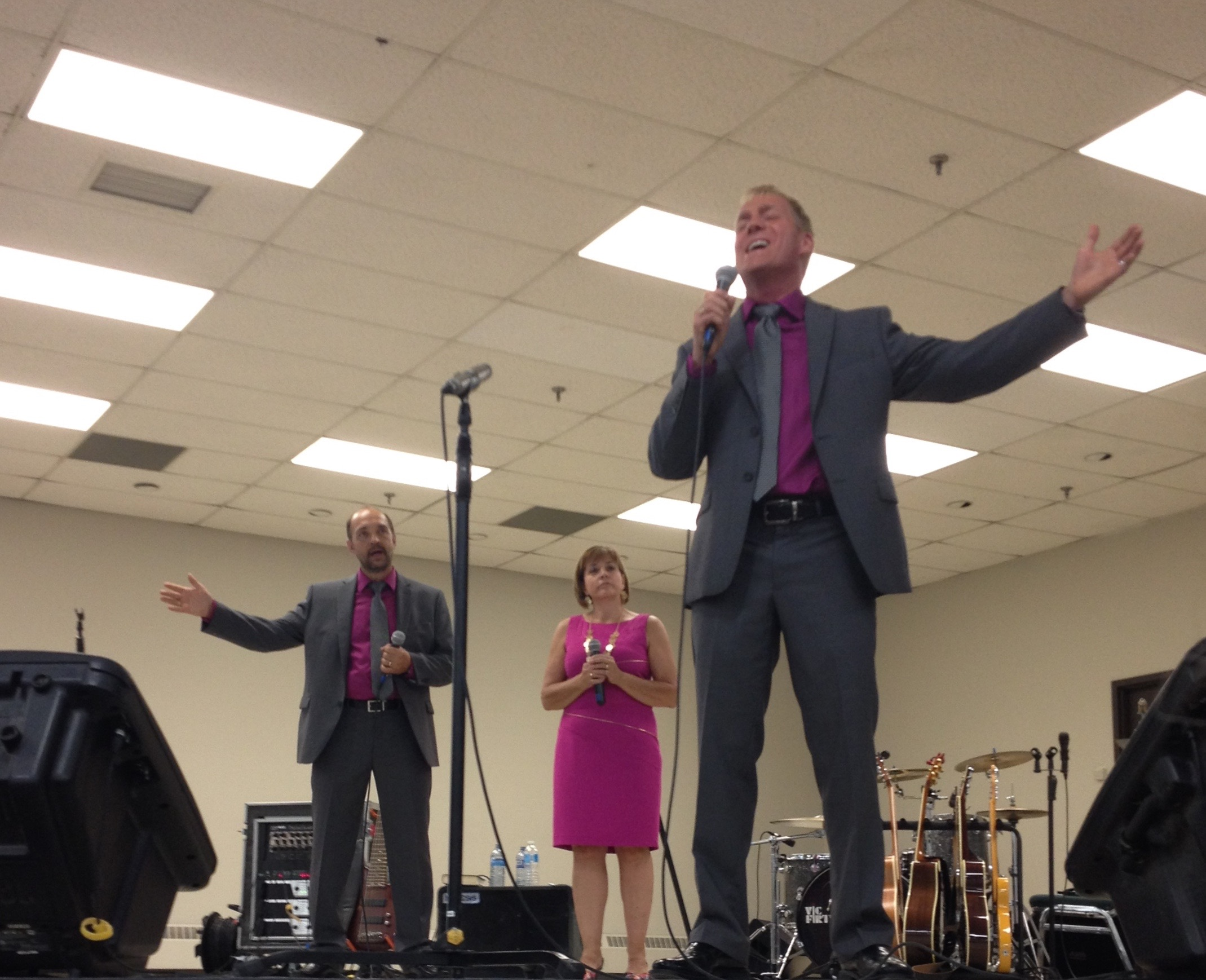 """Brent singing the 2nd verse to """"The Saviour Is Waiting"""" while Dianne and Dale watch.  Great crowd again this year at the Canadian showcase."""